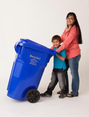 Woman and young child posing with a blue recycle bin.
