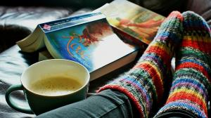 Image of feet with bright warm socks, a warm drink, and books