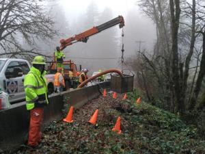 Road crew in bright safety gear watch a small crane lifting the end of a large pump hose over the embankment along the road.