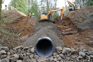 An exposed culvert at the bottom of a slope under construction, with two large excavators at the top.