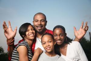 Father and three daughters smile at the viewer.