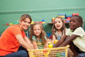 teacher playing with 4 children in her kindergarten class