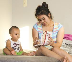 Hla Wah reads to her son, Hayson, 11 months.