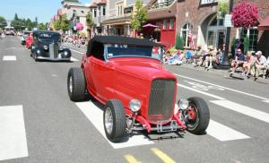 A red roadster leads a parade of classic cars through downtown Troutdale, with a crowd sitting on the sidewalk with an American flag.